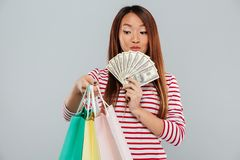 Surprised asian woman in sweater holding packages and money. Over gray background royalty free stock image