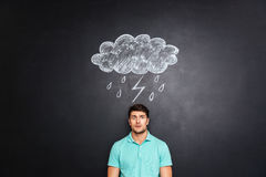 Surprised astonished man standing under raincloud drawn on blackboard background Royalty Free Stock Photography