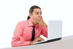 Surprised asustó al hombre joven con el ordenador portátil Imágenes de archivo libres de regalías