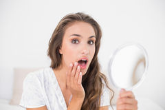 Surprised attractive brunette holding mirror Stock Photo
