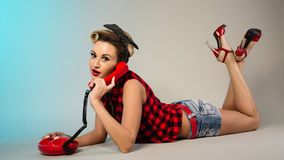 Surprised attractive girl in a plaid shirt and denim shorts talking on the phone lying on a gray background Stock Photo