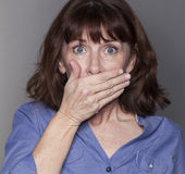 Surprised attractive mature woman hiding her mouth Stock Image