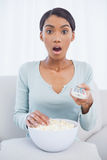 Surprised attractive woman eating popcorn while watching tv Stock Photo