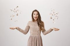 Surprised attractive young caucasian woman in evening dress tossing up confetti with both hands while glancing with. Opened mouth at camera over gray background Stock Photography