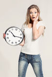 Surprised attractive young woman holding big clock Royalty Free Stock Photography