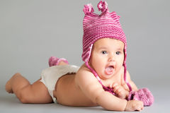 Surprised baby. In pink cap laying on gray background Stock Images