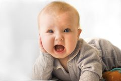 Surprised baby. Blue eyed baby with surprised open mouth smile Royalty Free Stock Photography