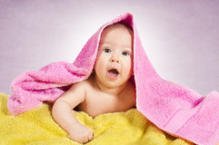 Surprised baby. Girl with towels on purple background Stock Photo