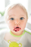 Surprised baby with beetroot puree around his mouth Stock Photography