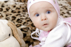 Surprised baby in a cap with a soft toy Stock Photography