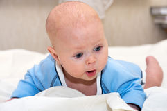 Surprised baby. Close up shot of boy lying on stomach Royalty Free Stock Photography