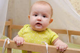 Surprised baby in a cot. Surprised cute baby standing in a crib stock photos