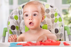 Surprised baby eating fruit - watermelon Royalty Free Stock Photography