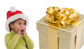 Surprised baby girl with one gift of Christmas. On a over white background Stock Images