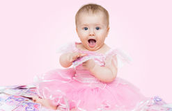 Surprised baby girl playing with money, on pink background Stock Photos