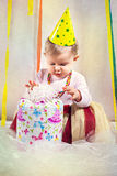 Surprised baby girl and birthday present. Surprised baby girl receiving present on first birthday Stock Image