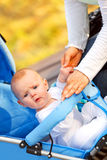 Surprised baby girl sitting in stroller in park. And holding mother's hand Royalty Free Stock Photography