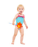 Surprised baby girl in swimsuit with pinwheel Stock Images