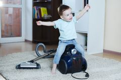 Surprised baby joyfully jumps on a vacuum cleaner while cleaning apartment