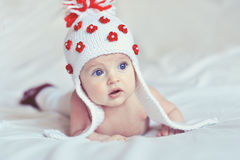 Surprised baby with knitted hat. Little surprised baby crawling on the bed with knitted hat Royalty Free Stock Image