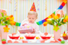 Surprised baby looking on gift on first birthday Stock Photography