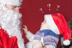 Surprised baby looking at Santa Claus, waiting for gift Royalty Free Stock Images