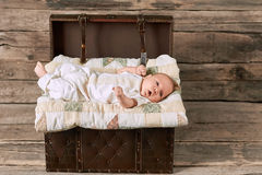 Surprised baby lying on blanket. Suitcase and child, wooden background. How babies see the world Stock Image