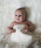 The surprised baby lying on white towel Stock Images