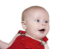 Surprised Baby in Red Overalls. A baby in red overalls looking to one side, surprised and happy. Isolated image Royalty Free Stock Image