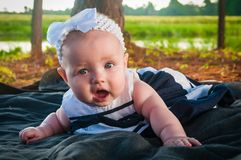 A Surprised Baby Sailor Girl. A surprised baby in a sailor dress outside on a blanket Stock Image