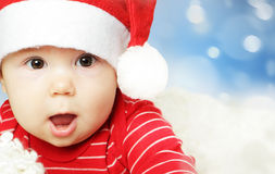 Surprised baby in Santa hat having fun, Christmas. And Happy New Year concept Royalty Free Stock Image