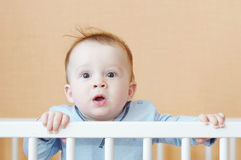 Surprised baby in white bed. Surprised baby age of 8 months in white bed Stock Photography
