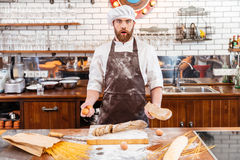 Surprised baker cutting bread and holding eggs on kitchen Stock Photo