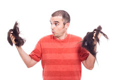 Surprised bald man holding his shaved hair Royalty Free Stock Images