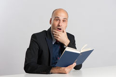 Surprised bald man reads a book Royalty Free Stock Image