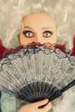 Surprised Baroque Woman Portrait with Wig and Fan. Baroque style portrait of a surprised beautiful woman behind a hand fan stock image