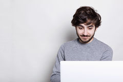 A surprised bearded hipster with modern hairstyle sitting in front of his laptop computer at home using Wi-Fi, looking amazed. Hum Stock Photography