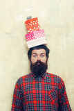 Surprised bearded man holding colorful gift boxes stacked on head. Surprised bearded man, caucasian hipster, with long beard and moustache in red plaid shirt Stock Image