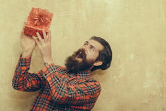 Surprised bearded man holding red gift box with bow. Surprised bearded man, caucasian hipster, with long beard and moustache in plaid shirt holding red gift box Stock Photo