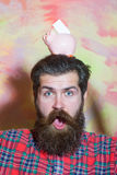 Surprised bearded man with pink ceramic piggy bank on head Stock Photo