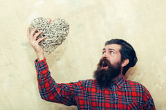 Surprised bearded man shouting with wicker heart. Surprised bearded man, caucasian hipster, with long beard and moustache in plaid shirt shouting with wicker Stock Photos