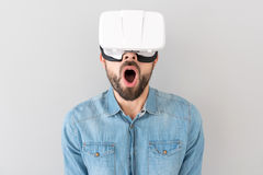 Surprised bearded man using virtual reality device Stock Images