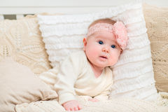 Surprised beautiful baby girl with chubby cheeks and big blue eyes wearing white clothes and pink band with flower lying on bed. With knitted pillows. Babyhood Stock Image