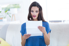 Surprised beautiful brunette reading letter Stock Images