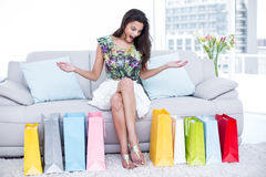 Surprised beautiful brunette sitting on the couch with shopping bags around her Stock Photo