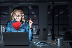 Attractive blonde wearing glasses in dark office using laptop. M. Surprised beautiful girl looking in glowing laptop screen. Mixed media stock image