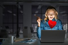 Attractive blonde wearing glasses in dark office using laptop. Mixed media. Surprised beautiful girl looking in glowing laptop screen. Mixed media stock photo