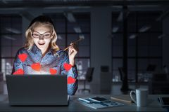 Attractive blonde wearing glasses in dark office using laptop. M. Surprised beautiful girl looking in glowing laptop screen. Mixed media royalty free stock photos