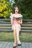 Surprised beautiful woman holding her planning-book posing outdoor.  Royalty Free Stock Images