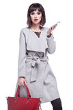 Surprised beautiful woman holding a phone. Dressed in a gray coat and holding a red bag Royalty Free Stock Photo